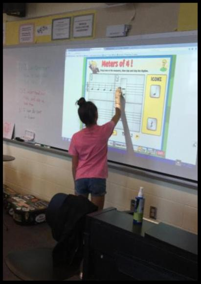 A student stands at a smart board and works on a program that says Meters of 4 at the top