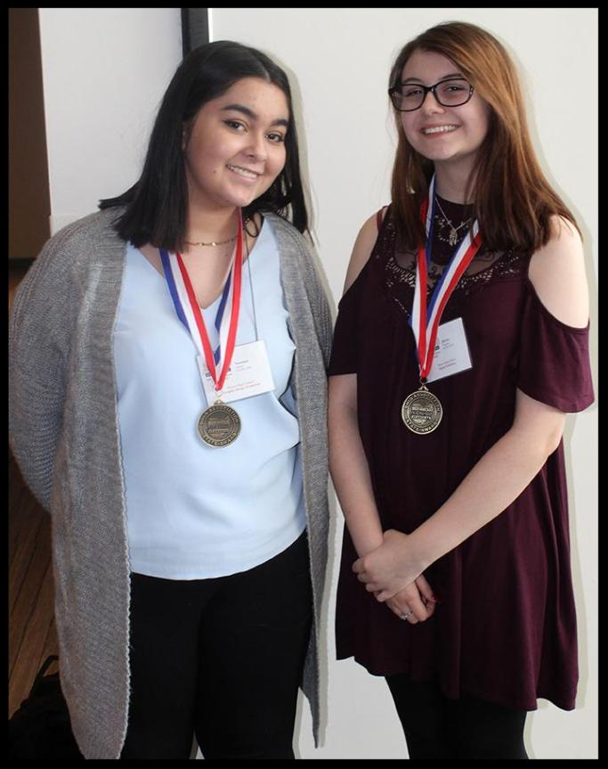 Two girls stand next to each other_ they are both wearing medals around their necks and smiling.