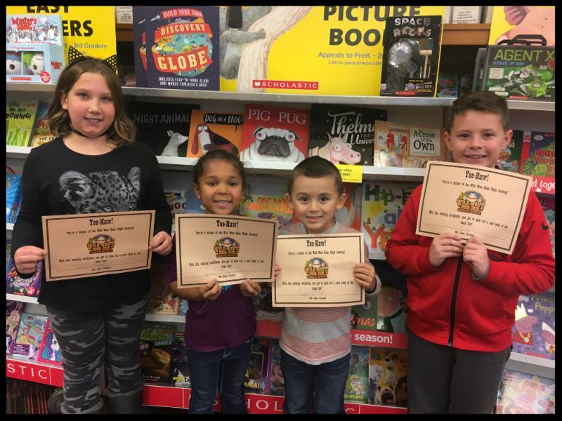 Four students stand in front of a bookshelf holding certificates and smiling at the camera