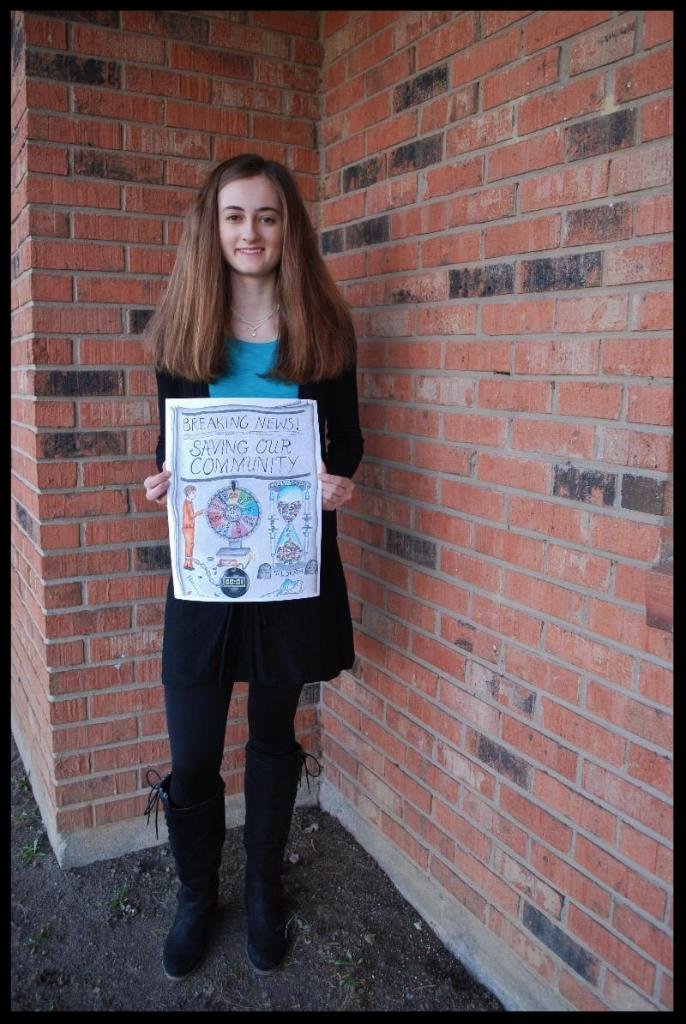 Abigail stands in front of a brick wall_ holding the poster she designed. It has the words _Breaking News Saving Our Community_ at the top_ with a drawing of a person in orange spinning a wheel next to an hour glass