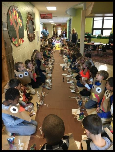 Students sit on the floor in a hallway. They stretch all the way down the hallway. There are students on either side_ facing each other. A long sheet of brown paper stretches down the hall that functions as a _table_
