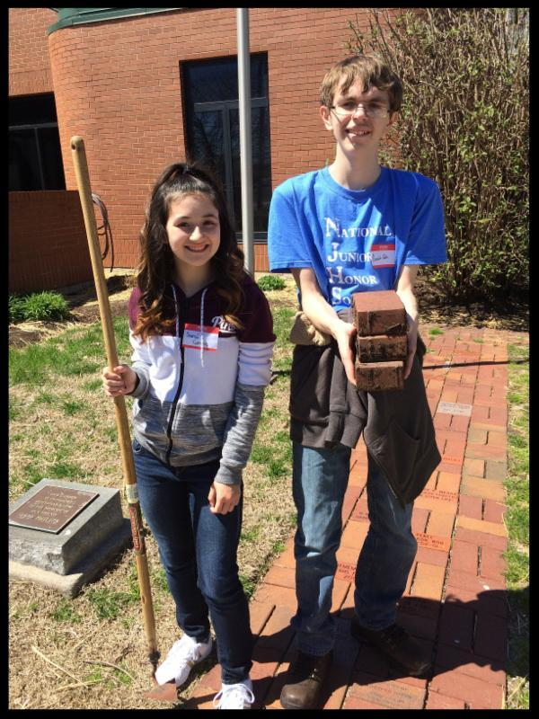 a student holding a shovel and a student holding pavers