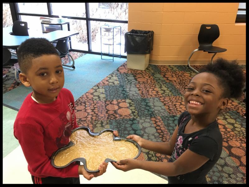 A young girl and a young boy are in a classroom. They are both holding a large gingerbread-man shaped pan with dough inside. The girl has a big grin.