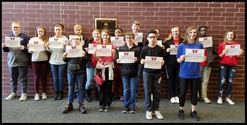 16 students stand in front of a brick wall holding up certificates.