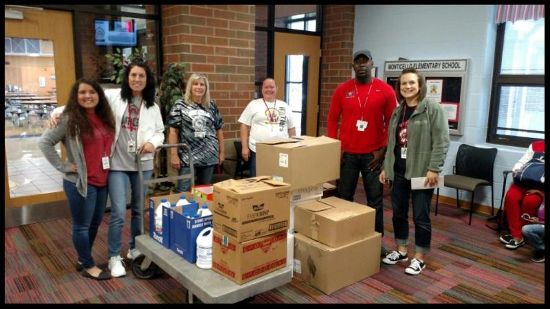 Staff members stand around large boxes that are sealed. They are standing in the school hallway.