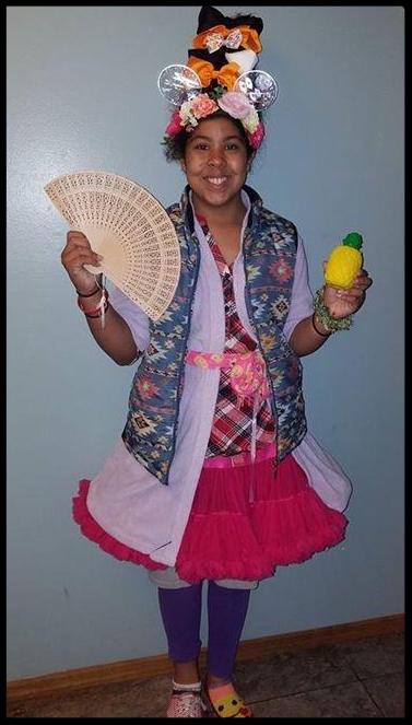 A student wears a tall hat covered in bows_ a vest with a busy patter_ a pink tutu skirt_ purple leggings and mismatched shoes. She holds a fan in one hand and a bottle of pineapple juice in the other.