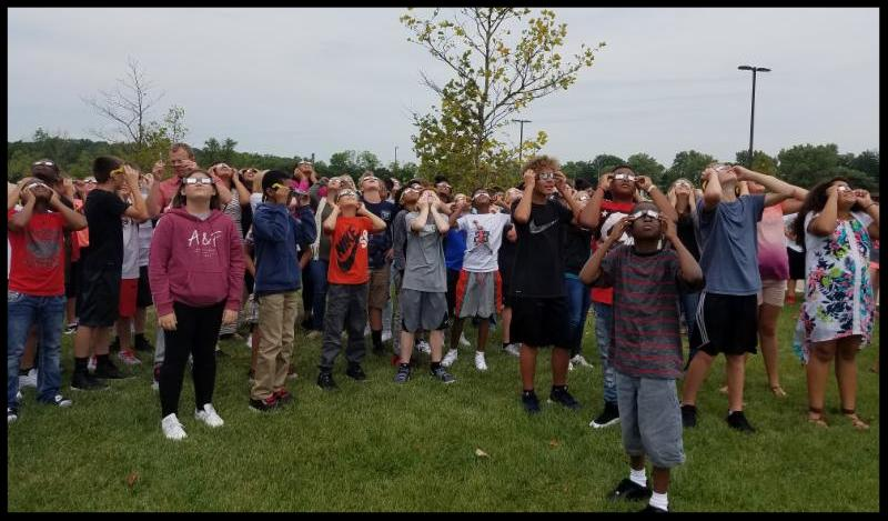 A group of students wearing eclipse glasses and lookng up at the sky