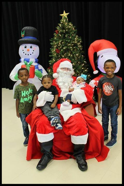 Santa holds a young boy and an infant on his lap_ while two boys stand on either side of him. There is a Christmas tree_ an inflatable snowman and an inflatable Snoopy wearing a Santa hat behind them.