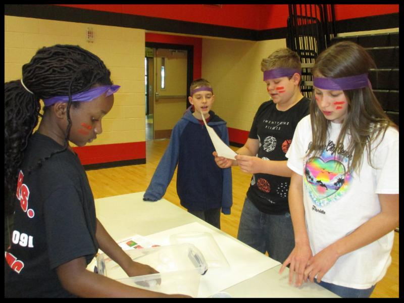 Four students are standing around a table. Two of them appear to be talking to each other. The students are wearing purple headbands and have two stripes of red facepaint on either cheek