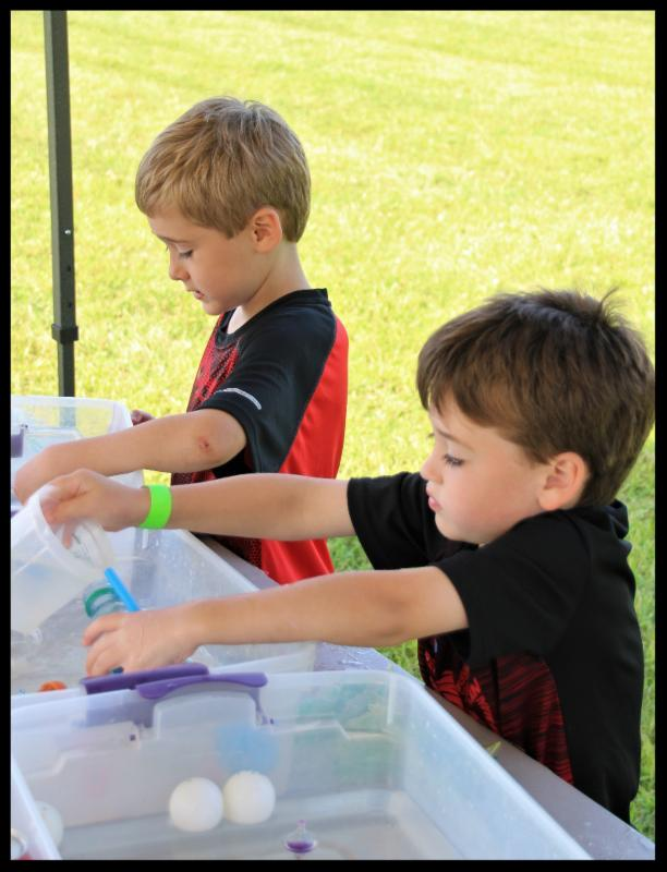 Two young boys study bouyancy by floating balls in plastic containers filled with water