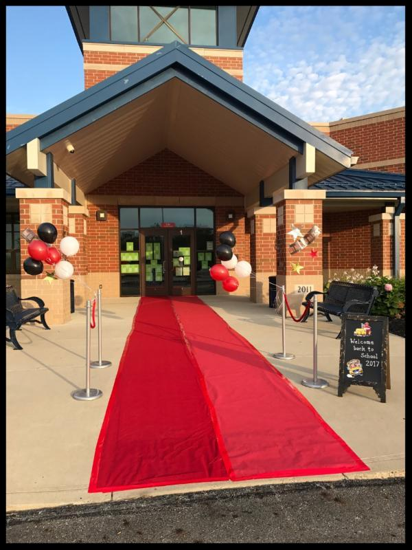 Exterior shot of the building with a red carpet leading to the front door