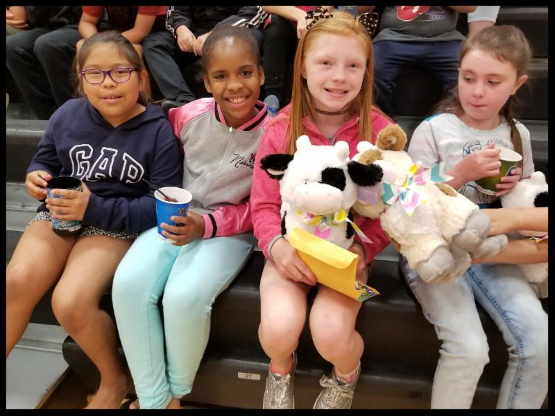 Four girls sit on a bleacher. Three are holding cups of shaved ice from the Kona ice truck. One is holding a stuffed cow