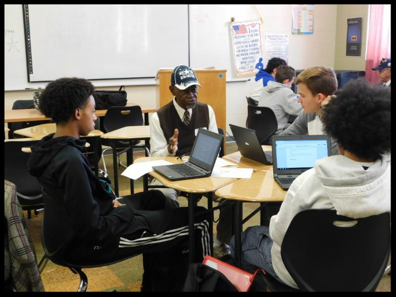 Three students sit at with their desks in a circle with laptops in front of them. They are listening to an older man talk.