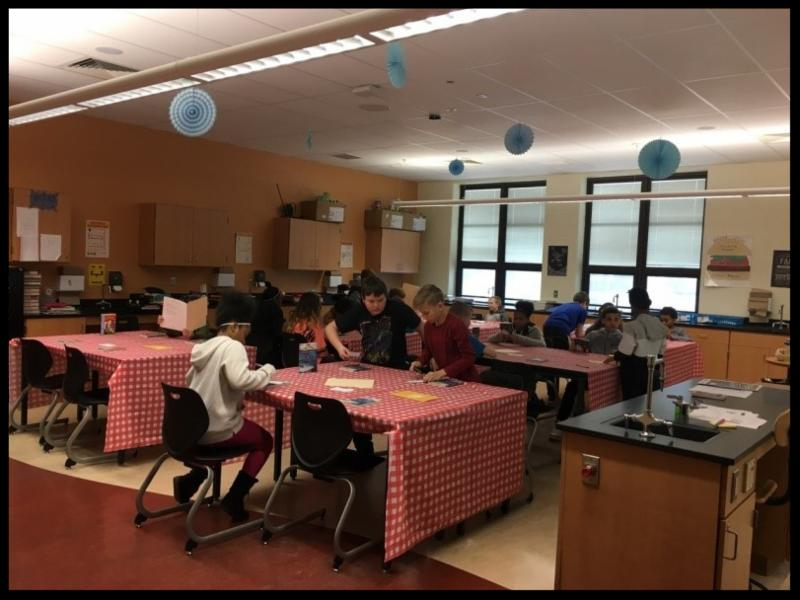 Students are gathered around tables in a classroom. The tables have checkered red-and-white tablecloths like a diner. They are reading pieces of paper on the tables.