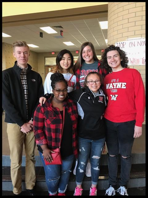 A group of six students stand in a group smiling at the camera