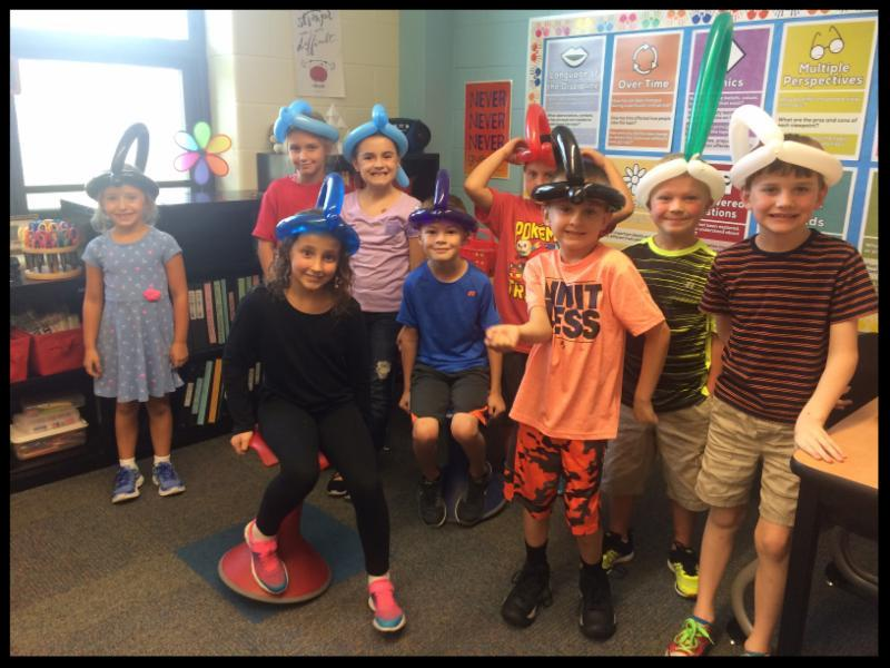 A group of students smile at the camera. They are in a classroom. They are wearing balloon hats on their heads.
