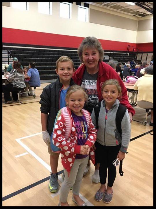 A lady standing with her three grandkids_ all are smiling at the camera