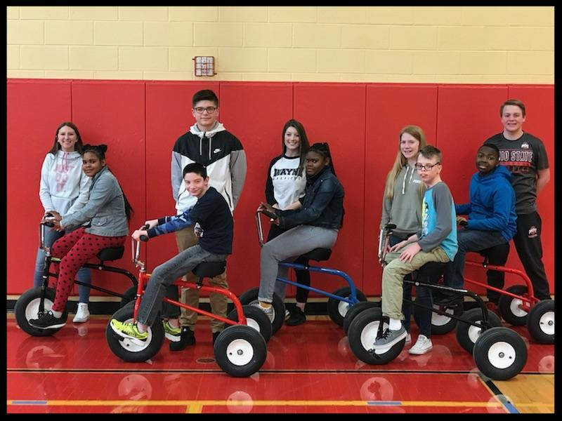 Five students are sitting on bikes looking at the camera. Behind them stand a line of five students who are smiling.