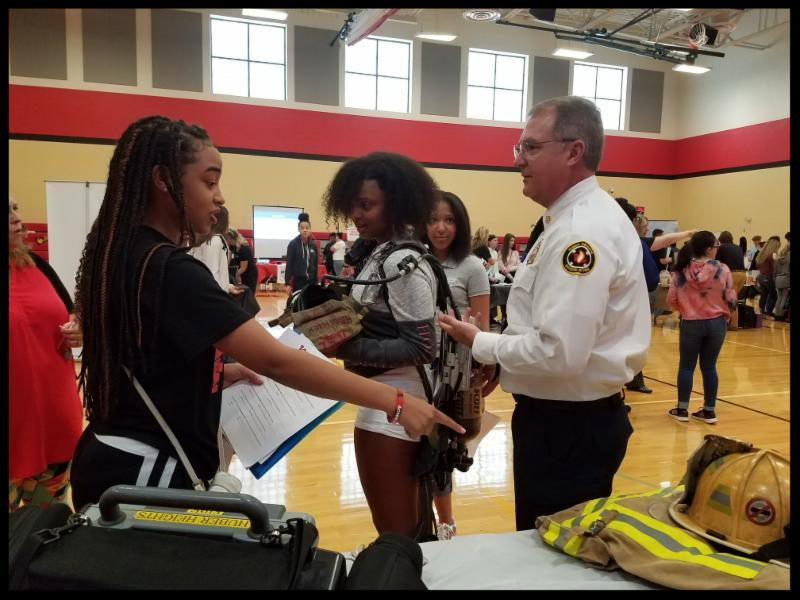 Two students talk to a fire chief