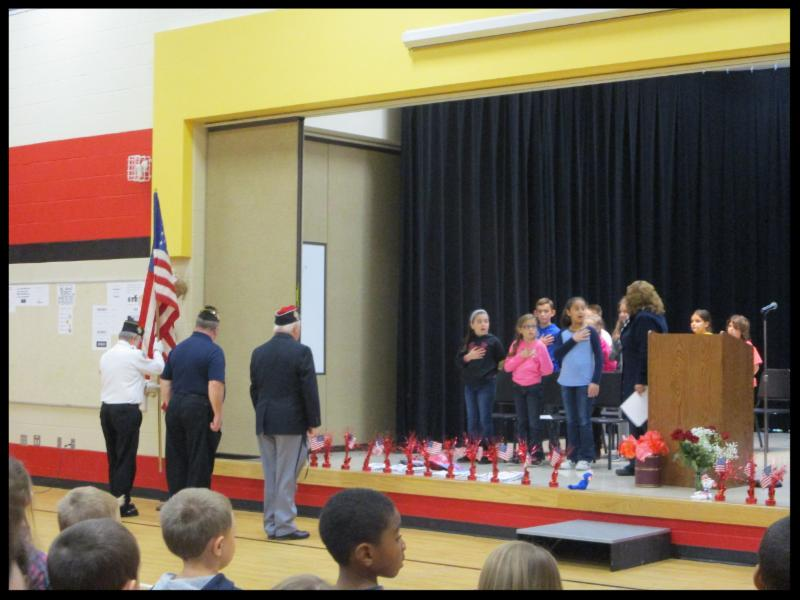 Students stand on a stage_ with their hands over their hearts_ singing. Three members of the VFW stand facing them.