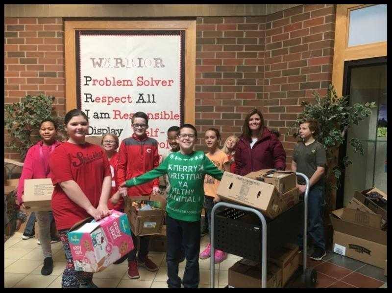 A group of students stand in the atrium holding boxes of canned goods. There is also a car loaded with boxes
