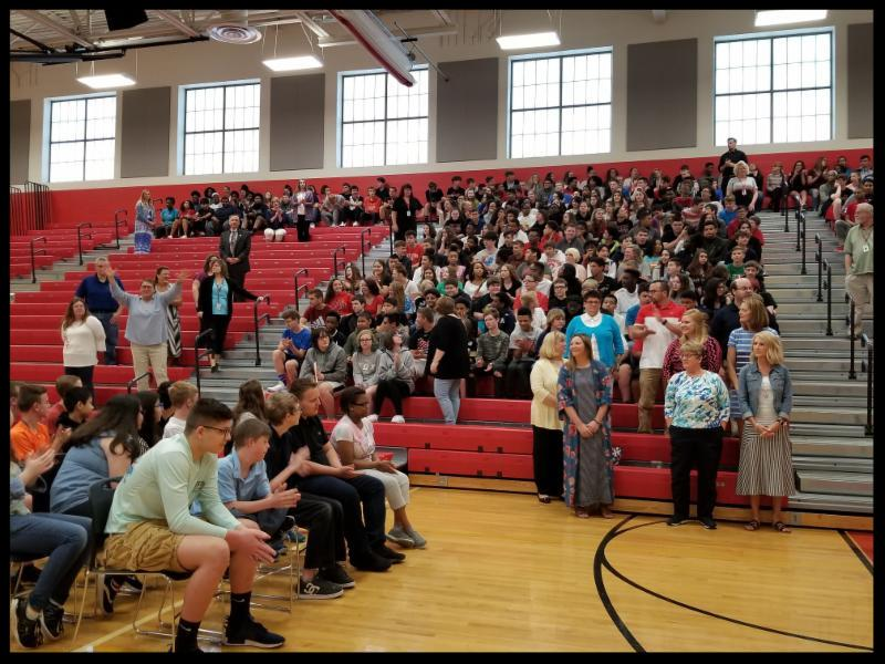 This image was taken inside the gymnasium. It shows students sitting on chairs on the floor and parents and_or staff sitting in bleachers.