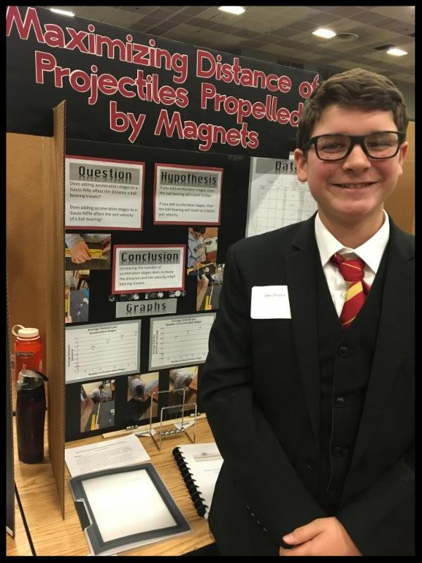 A student standing in a suit coat and tie smiles next to his display_ which is titled Maximizing Distance of Projectiles Propelled by Magnets