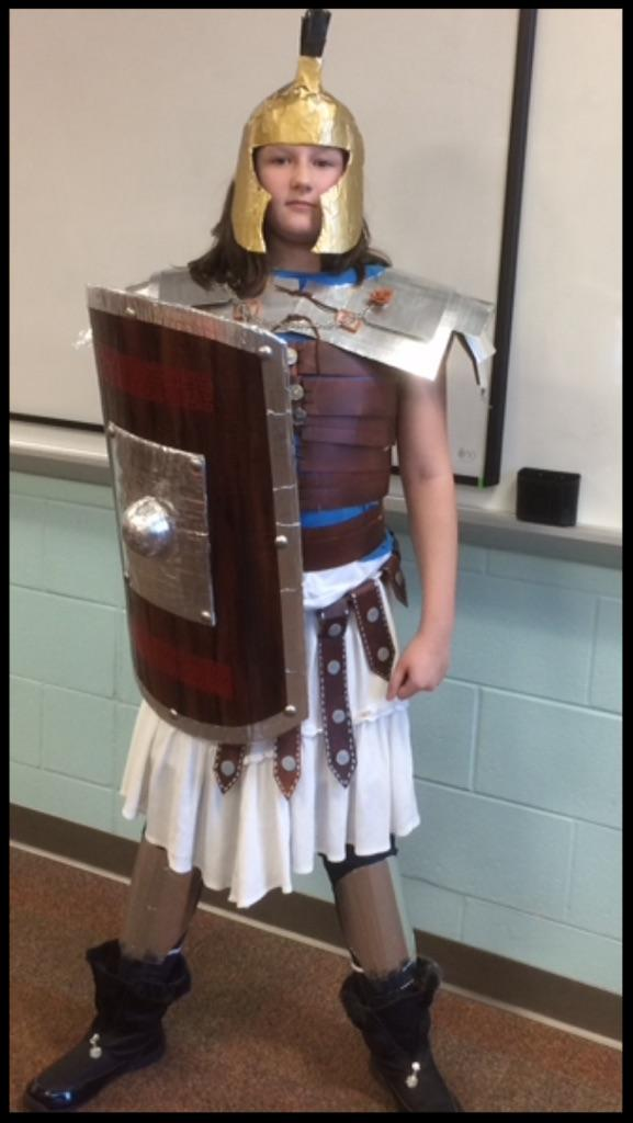A boy stands in a costume of a Roman soldier