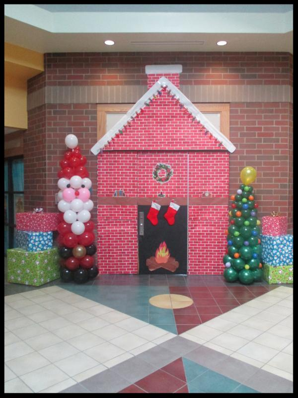 A replica of a brick house with a fireplace with stockings hanging on the mantle is placed in the school_s atrium_ it is flanked by a santa made out of balloons and a christmas tree made out of balloons.
