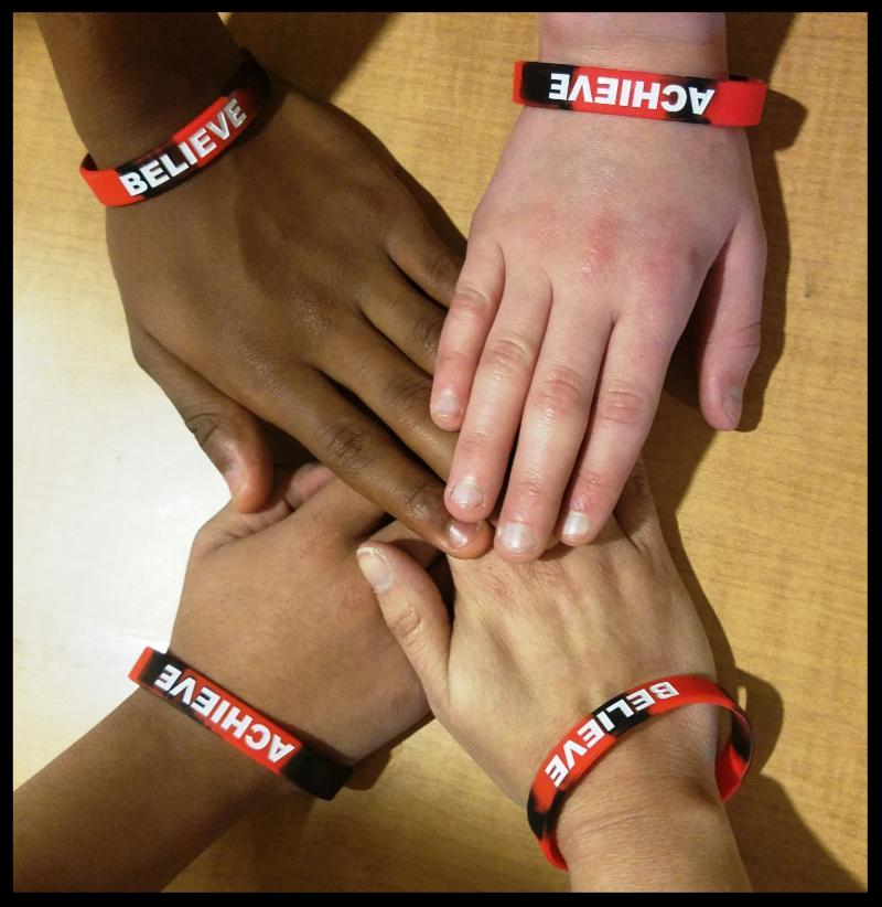 Four hands touch in the center of a table. Each wrist includes a wristband - two of which read Achieve and two of which read Believe