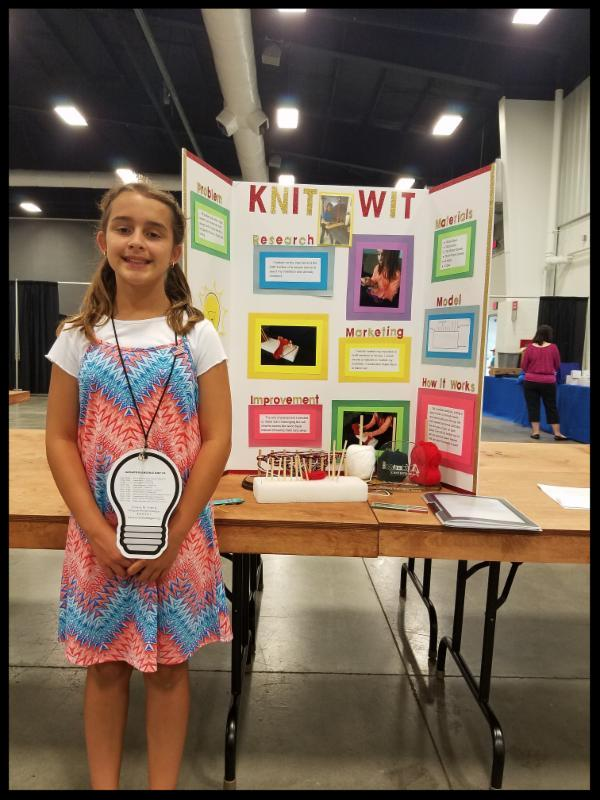 A young girl stands in front of a display that has the words Knit Wit at the top. She is smiling and wearing a badge shaped like a lightbulb around her neck.