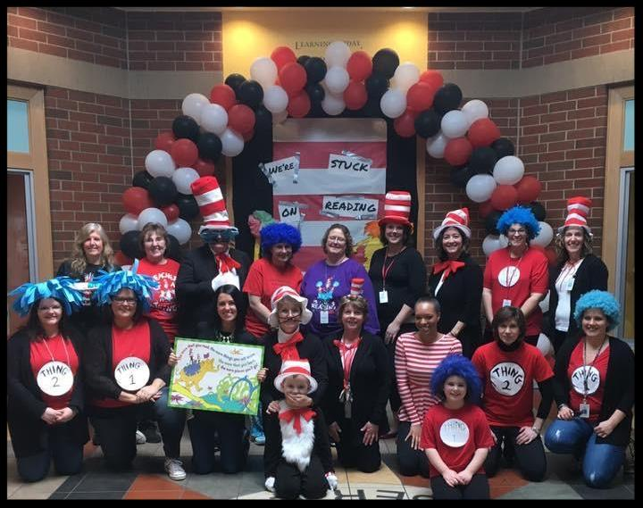 Students and staff pose in front of a red_ white and black balloon arch. They are dressed in Cat in the Hat themes - as Cat in the Hat_ with black and white clothes_ red bow ties and red-and-white striped stovepipe hats_ and as Thing 1 and Thing 2_ wearing red shirts that say Thing 1 or Thing 2 and blue wigs.