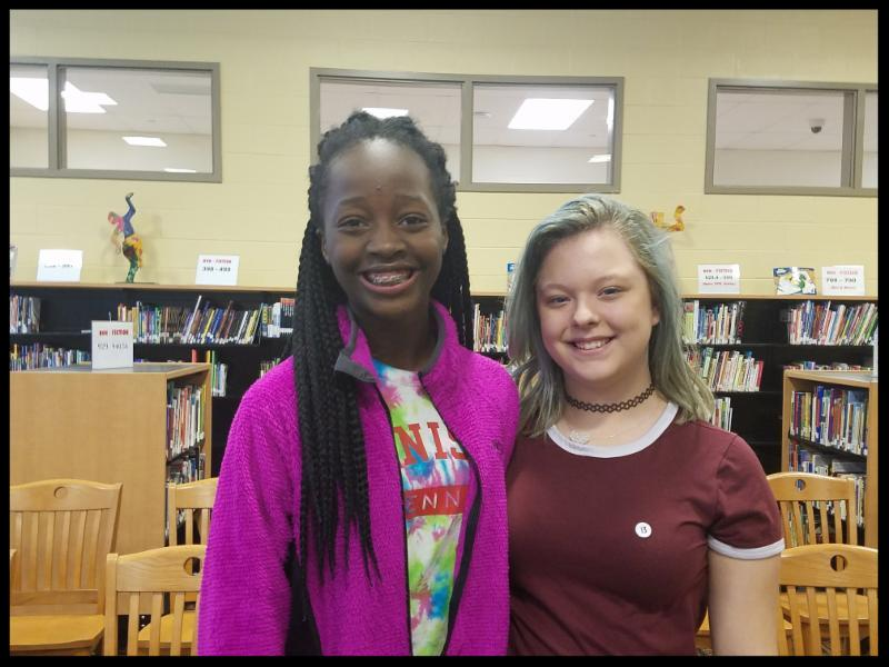 Two girls stand side by side_ smiling at the camera. They are in the media center_ there are shelves of books in the background.