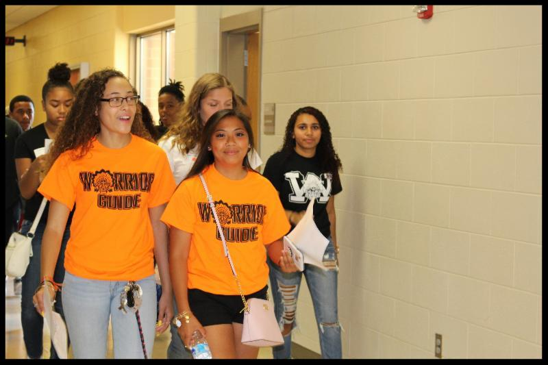 Two female students wearing orange shirts that say _Warrior Guide_ are leading a group of other students down a hall and everyone is smiling