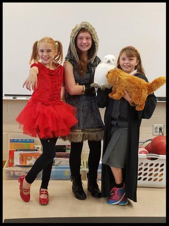 Three girls are dressed up. One is in a red frilly dress with black leggings and red shoes_ one is in a velvet and fur hooded cloak holding a stuffed owl_ the third is wearing a robe and holding a stuffed cat.