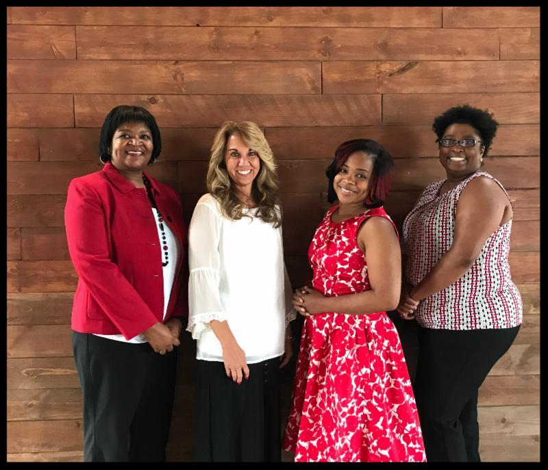 Four new administrators smiling at the camera