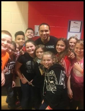Special guest Donnie Ray Evege stands with a group of students_ all smiling at the camera