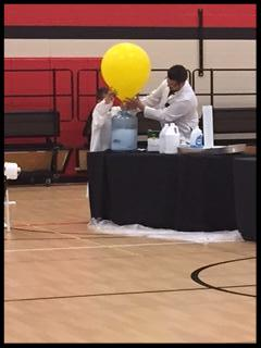 Mr C and a student inflate a giant balloon