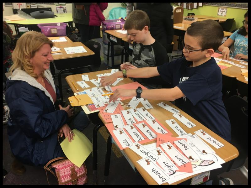 A boy sorts flash cards that have words on them while a woman looks on and smiles.