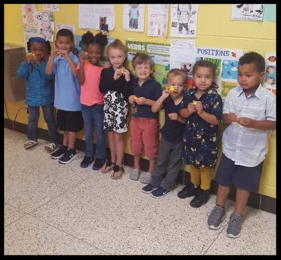 Eight preschoolers stand in a line against a wall. They are holding little rubber duckies and smiling at the camera
