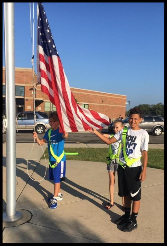 Three students stand in front of the school. The sun is bright.. They are wearing bring green safety patrol harnesses. They are holding the flag and preparing to raise it for the day.