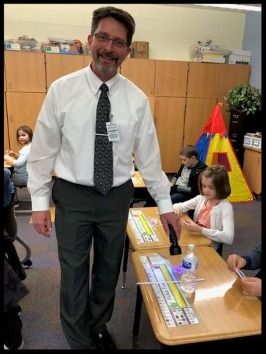 A man is standing in a classroom smiling at the camera. In one hand he holds a flashlight_ which he is shining down on some beads on a desk.