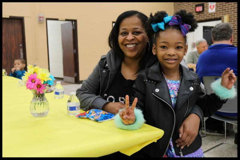 A little girl with purple and blue bows in her hair is standing next to her grandmother. They are sitting at a cafeteria table that is covered in a yellow tablecloth. There is a vase with flowers on the table.