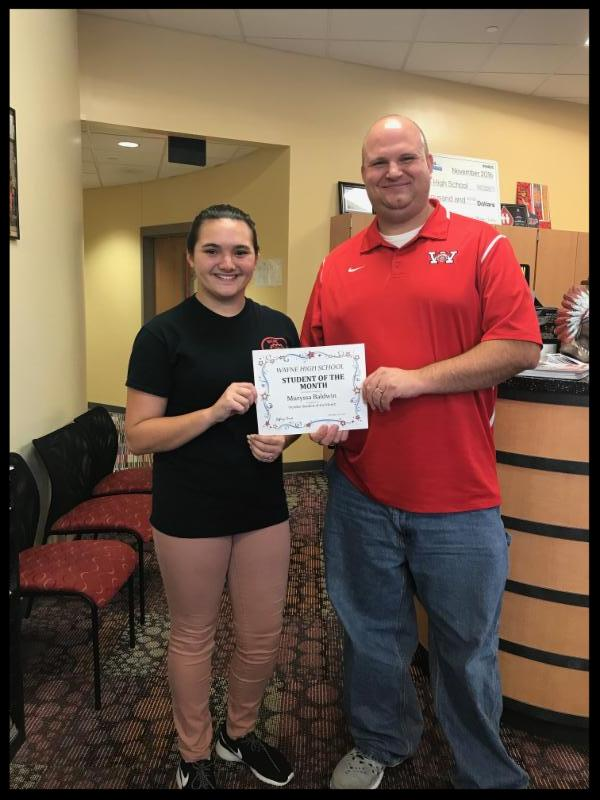 Muryssa stands next to principal Berk. They hold a student of the month certificate between them.
