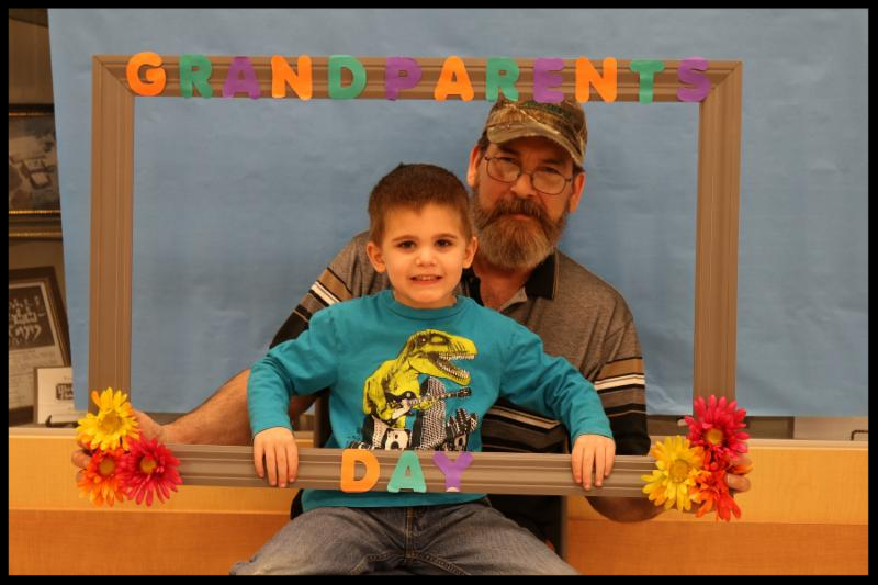 A boy sits on his grandfather_s lap. They are holding a large brown frame around them. The top of the frame says Grandparents and the bottom of the frame says Day. There are flowers glued to the corners of the frame.
