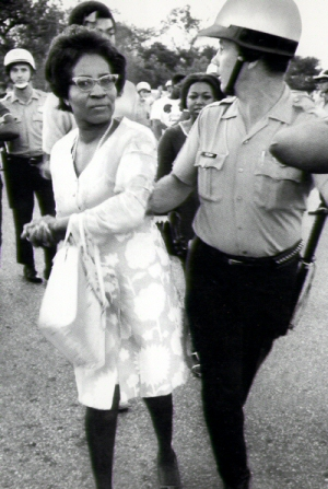 Black woman led by police officer
