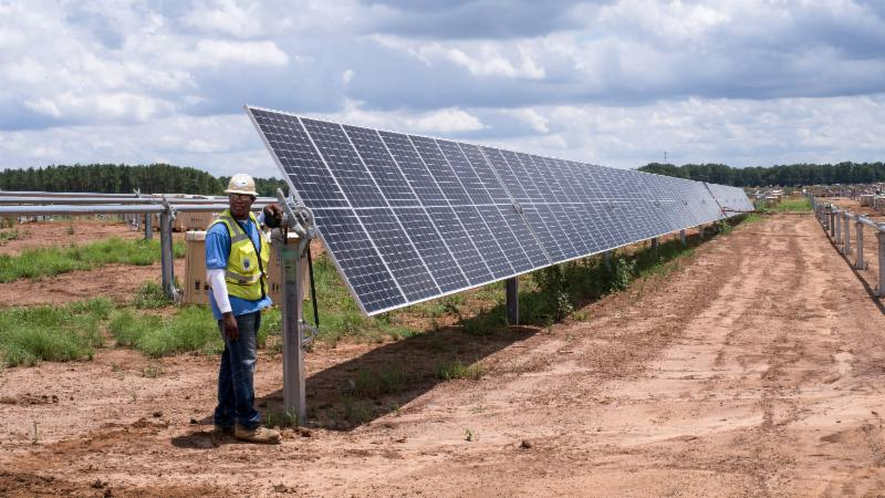 man standing next to solar panels
