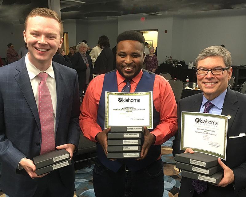 three men holding certificates