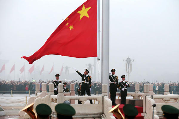 Chinese flag on flagpole with solders saluting