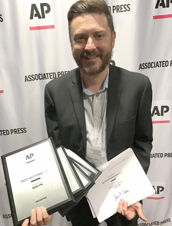 man holding stack of plaques and certificates